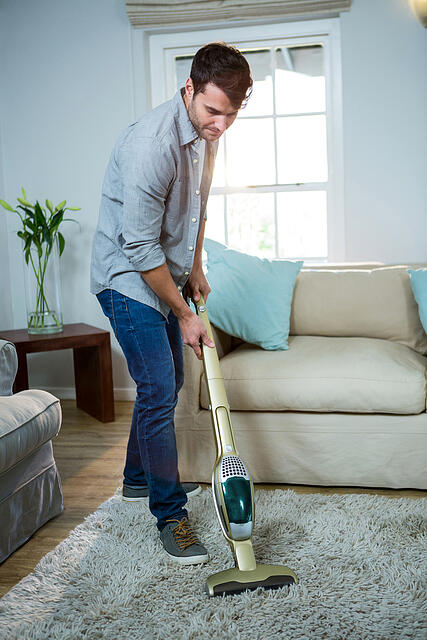 Man cleaning a carpet with a vacuum cleaner at home